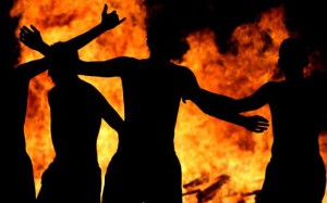 People dance around a bonfire during traditional San Juan's (Saint John) night in Torre de Benalgabon, southern Spain, June 24, 2005. Fires are lit throughout Spain on the eve of Saint John where people burn objects they no longer want and make wishes as they jump through the flames. REUTERS/Rafael Marchante